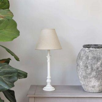 Antique white tablel lamp with linen shade on a table next to a pot.