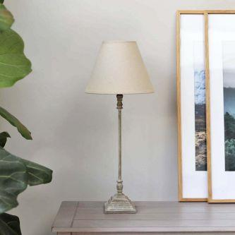 Natural thin table lamp with shade on a table next to a picture frame.